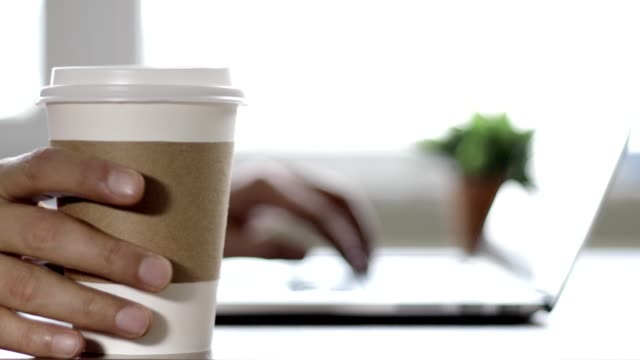 man working on laptop, he pauses for a coffee break - coffee drink stock videos & royalty-free footage