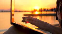 Man working on laptop near the sea. Male with notebook on sunset background. Freelancer working on the nature. Programmer background. Distant job background. Quality of Network connection concept