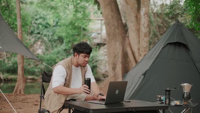 vidéos et rushes de un homme travaillant sur l'ordinateur portatif sur la nature au camping - activité de plein air