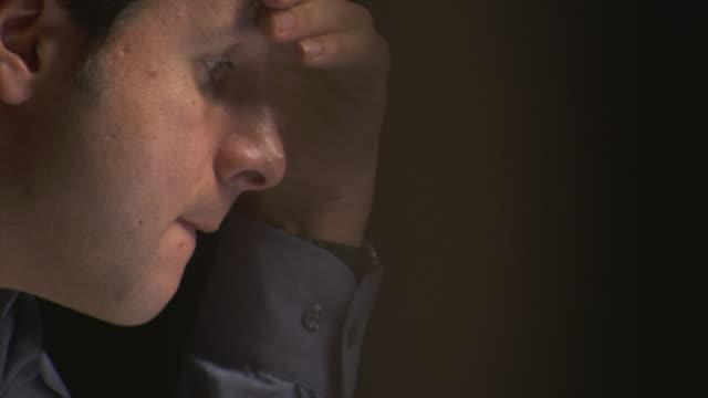 ecu, tu, selective focus, man working on laptop seen through blinds - tired stock videos & royalty-free footage