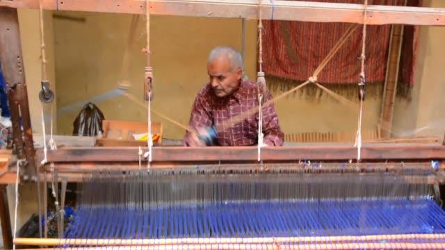 man working on loom machine in silk factory in morocco fez - ワーキングシニア点の映像素材/bロール