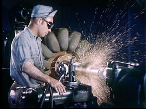 vídeos y material grabado en eventos de stock de composite, man working on machine in factory, sparks spraying, 1950's, oklahoma, usa - sparks