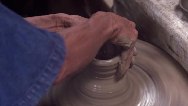 man werkt op Potter Wheel en beeldhouwen Clay po