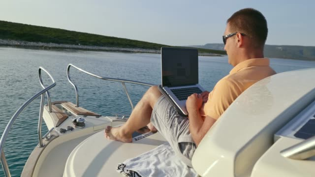 man working on the laptop while sitting on the bow of his boat - one mature man only stock videos & royalty-free footage