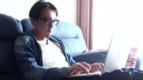 vidéos et rushes de a man working on the sofa at home - politique