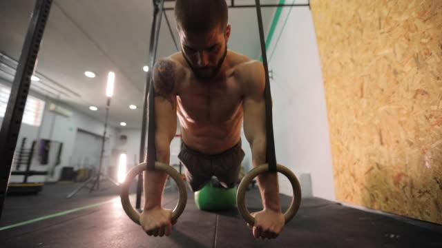 trainieren sie im fitnesscenter mit gymnastik ringen mann - halbbekleidet stock-videos und b-roll-filmmaterial