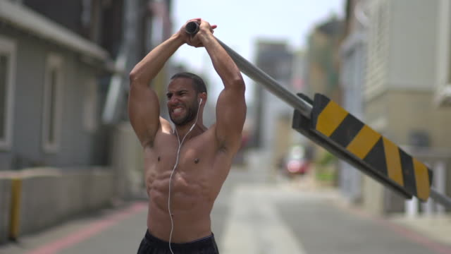 A man working out in an urban alley, doing shoulder press with a road barricade bar. - Slow Motion