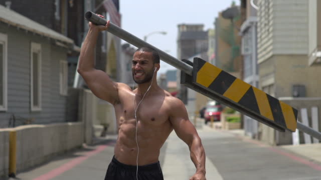 a man working out in an urban alley, doing shoulder press with a road barricade bar. - slow motion - boom barrier stock videos & royalty-free footage