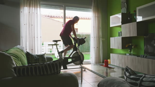 man working out on exercise bike at home - exercise machine stock videos & royalty-free footage