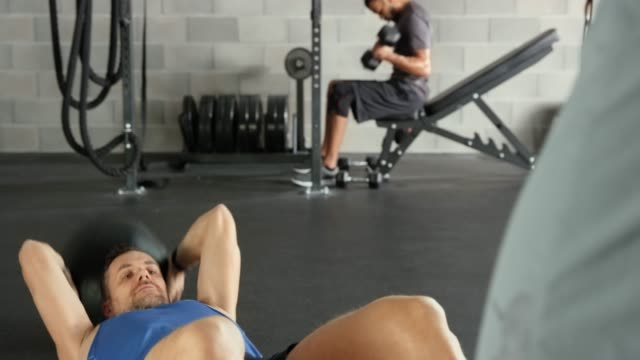 Man working out with a medicine ball with the help of his trainer in the gym