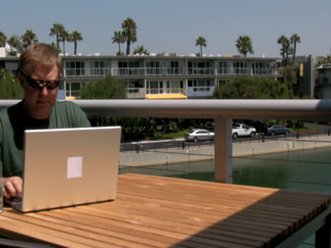 stockvideo's en b-roll-footage met man working outside, closes laptop and walks away - dicht