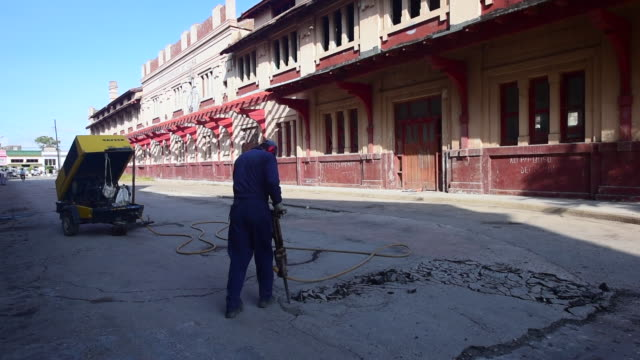 man working pneumatic hammer in the camaguey train station which is a heritage building under repair or revitalization / cuba has become an important... - tourist train stock videos and b-roll footage