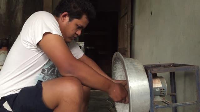 Man working to scrape coconut