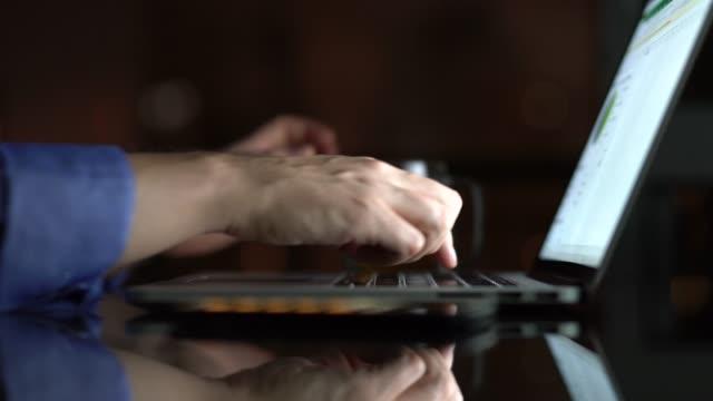 vídeos de stock, filmes e b-roll de homem trabalhando / usando laptop em casa à noite - surfar na net