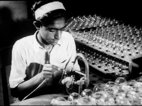 man working w/ incandescent light bulbs lifting bulb from spinning rack soldering exterior end tip by hand ls workers sitting at long table rolling... - incandescent bulb stock videos and b-roll footage