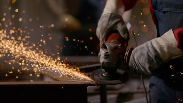 stockvideo's en b-roll-footage met slo mo td man working with an angle grinder - metaalindustrie
