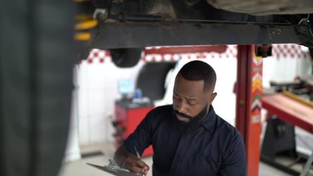 vídeos y material grabado en eventos de stock de hombre que trabaja con portapapeles en el taller de reparación de automóviles - mecánico de coches