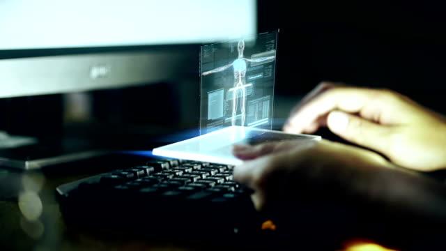 男はホログラフィック フェースで人間の体の作業と自宅の暗い部屋でキーボードで入力します。