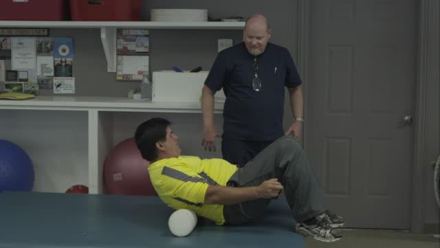 vídeos y material grabado en eventos de stock de man working with physical therapist on back roller. - espalda humana