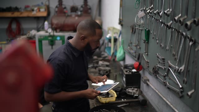 man working with tablet in auto repair - repairman stock videos & royalty-free footage