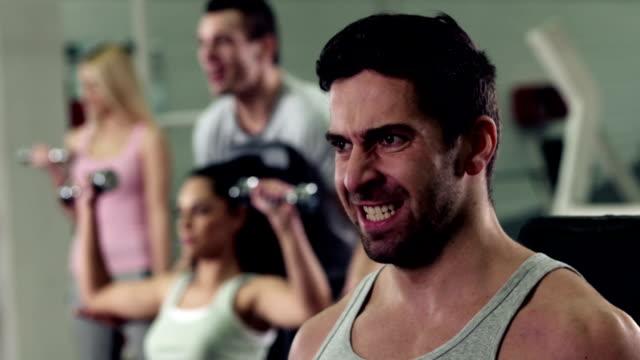 vidéos et rushes de homme travaillant avec les poids et haltères dans la salle de sport - poids pour la musculation