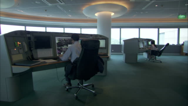A man works at a computer terminal in a control room.