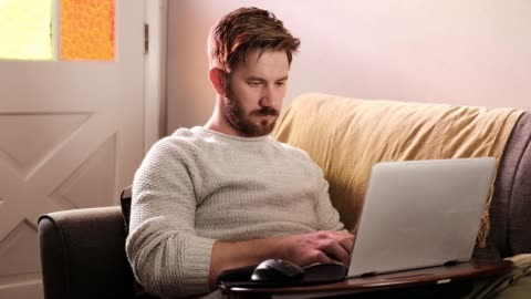 a man works from his couch - moving shot - typing stock videos & royalty-free footage