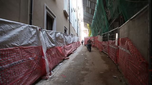 A man works in the historic center of L'Aquila on March 21 2017 The Eighth anniversary of the L'Aquila earthquake will be marked on 06 April 2017...