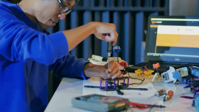 a man works on a fully functional programable robot for robotics club project.creative designer testing robotics prototype in workshop.innovation,science concept.industry 4.0 - industrial revolution stock videos & royalty-free footage