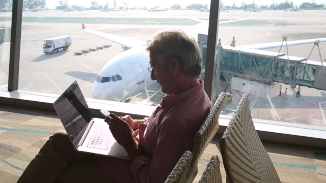 Man works on laptop computer, in airport setting