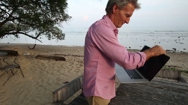 Man works on laptop computer, looks over sea