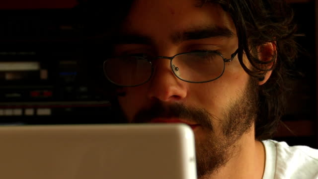 man works on laptop - reading glasses stock videos & royalty-free footage
