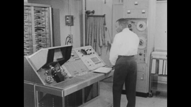vidéos et rushes de 1960 man works the controls of a microfilm machine, feeding cenus information into optical sensing device - audio disponible en ligne