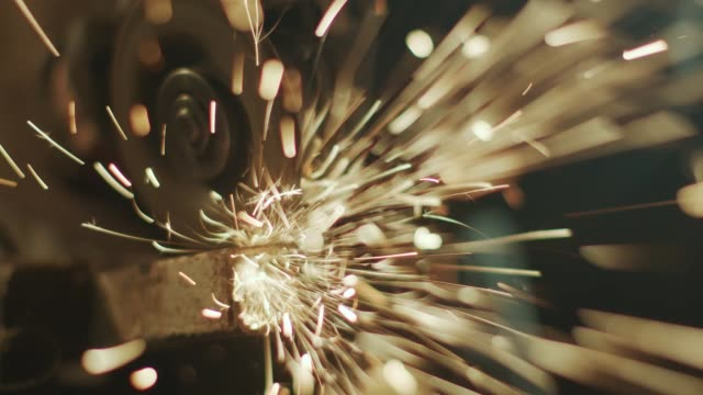 man works with a grinder in his garage making incredible sparks - stock video - tecnico video stock e b–roll