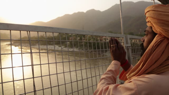 vídeos de stock, filmes e b-roll de man worshipping in river, ganges river, laxman jhula, rishikesh, uttarakhand, india - rishikesh