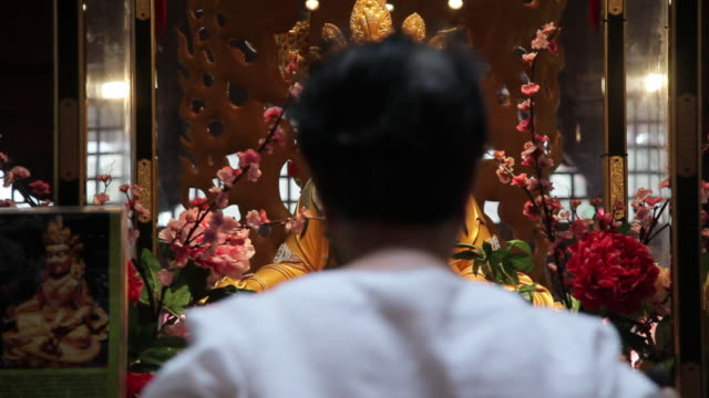 a man worships at a shrine in the buddha tooth relic temple and museum in singapore. - shrine stock videos & royalty-free footage