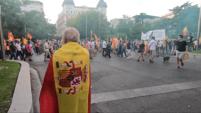 vídeos y material grabado en eventos de stock de man wrapped up in a spanish flag walks down paseo de la castellana, one of the city's main avenues, during a demonstration against the government on... - imágenes