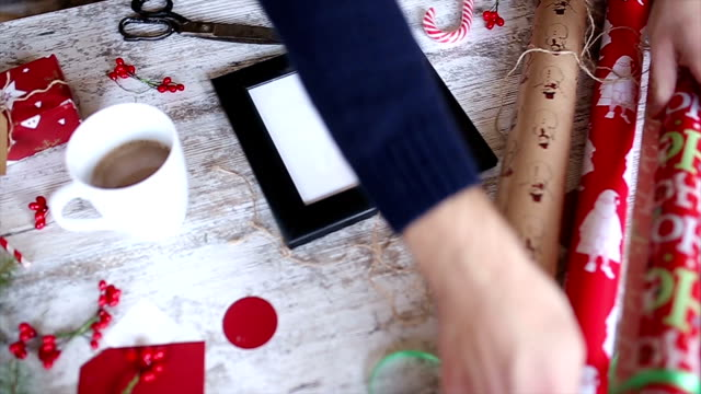 Man Wrapping Christmas Gifts At Home