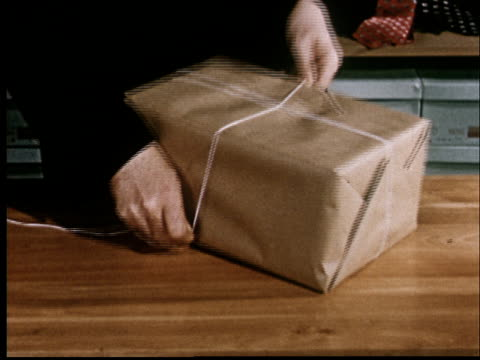 vidéos et rushes de cu, man wrapping string around brown package on counter - kraft