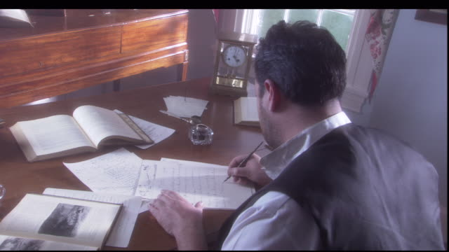 a man writes a letter with an ink dip pen on a desk covered with books and papers. - pen and ink stock videos & royalty-free footage