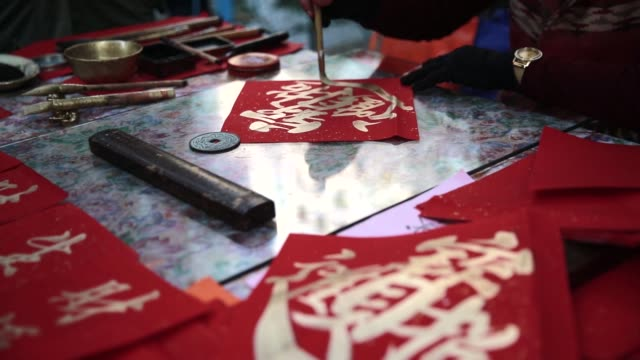 vídeos y material grabado en eventos de stock de a man writes chinese calligraphy on decorations for lunar new year at a market stall in the sheung wan district of hong kong china on thursday feb 4... - sheung wan