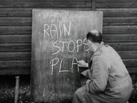 A man writes Rain stops play onto a blackboard at an outdoor sporting event 1953