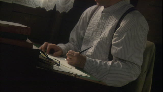 a man writes with a fountain pen at an old fashioned writing desk. - reenactment stock videos & royalty-free footage
