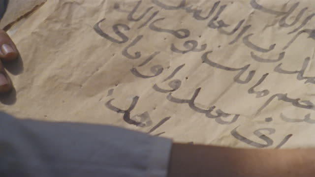 CU RECREATION Man writing Arabic text on paper with quill pen / Iran
