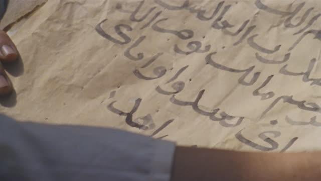 cu recreation man writing arabic text on paper with quill pen / iran - arabic script stock-videos und b-roll-filmmaterial