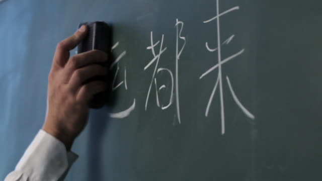 CU Man writing Chinese characters on blackboard / Singapore