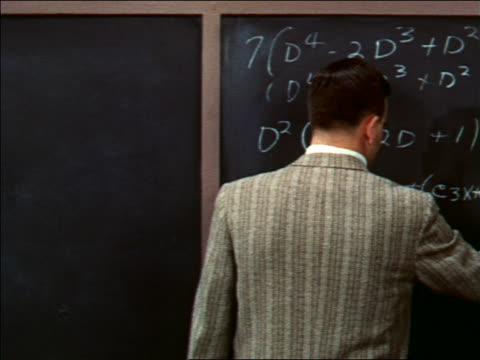 1956 man writing equations on chalkboard + turning around toward camera