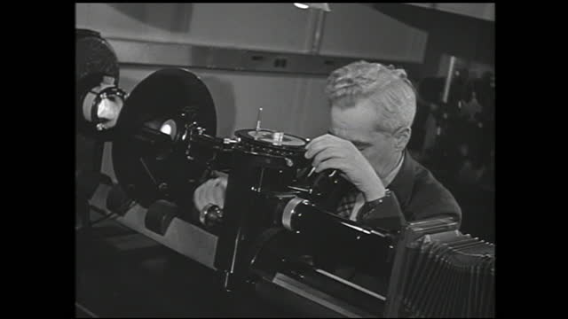 man writing formula on blackboard while talking to another man, man looking through microscope, and crystal on machinery - 1940 1949 stock videos & royalty-free footage