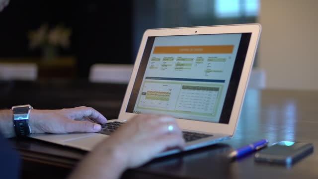 vídeos de stock e filmes b-roll de man writing in laptop in the office - olhar por cima do ombro
