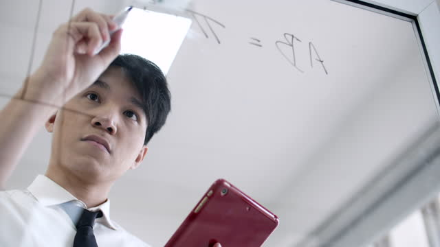 mann schreibt notiz und ideen auf glasbrett - völlig lichtdurchlässig stock-videos und b-roll-filmmaterial